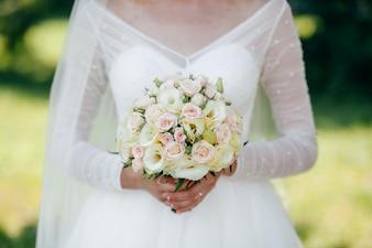 Mariée et marié avec un bouquet de fleurs rouges et de verts en main