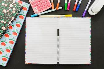 Marqueurs et papier blanc avec calculatrice et agrafeuse