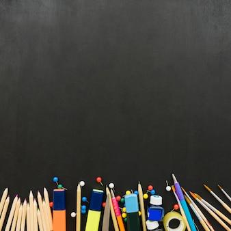 Matériel scolaire sur bureau noir