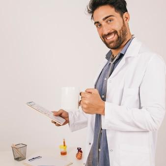 Médecin souriant posant avec ipad et café