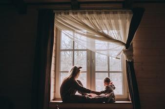 Mère avec bébé assis à la fenêtre et jouer