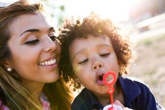 Mère avec son fils faire des bulles de savon