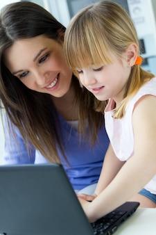 Mère et fille utilisant un ordinateur portable dans la cuisine