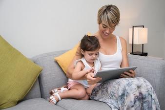Mère joyeuse montrant le jeu sur la tablette à la fille