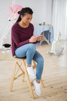 Message de jeune femme concentré sur le téléphone