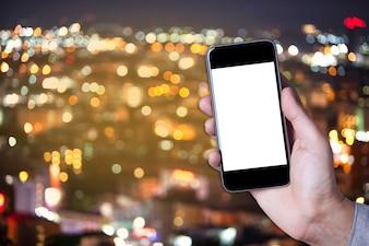 Mettez une partie de l'homme tenant l'écran vide de smartphone avec l'arrière-plan de bokeh de la ville.