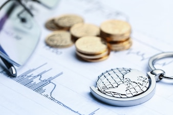 Monnaies, billets et globe sur fond blanc