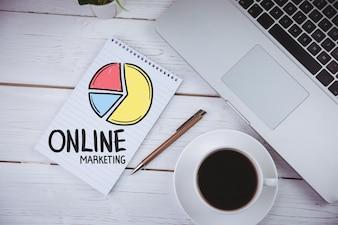 """Notebook avec les mots """"marketing en ligne» et une tasse de café"""