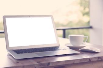 Ordinateur portable avec écran blanc sur une table en bois et une tasse de café