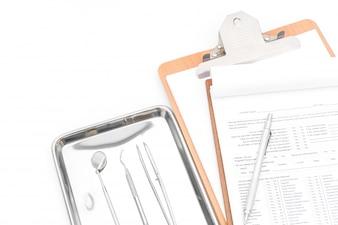 Outils dentaires, matériel et tableau dentaire sur fond blanc