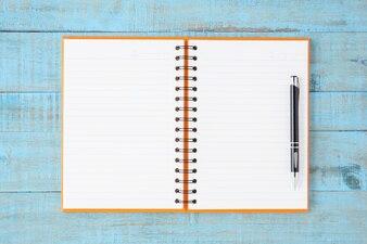 Ouvert orange Carnet et stylo sur table en bois bleu
