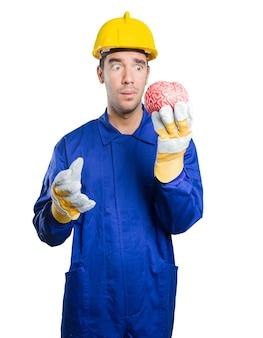 Ouvrier égaré tenant un cerveau sur fond blanc