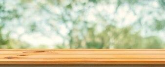 Panneau de bois table vide fond flou. Perspective table en bois brun sur fond de forêt des arbres flou - peut être utilisé maquette pour l'affichage ou le montage de vos produits. saison de printemps. bannière panoramique.