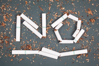 Panneau de non-fumeur fabriqué avec des cigarettes brisées et du tabac sur le tableau noir.