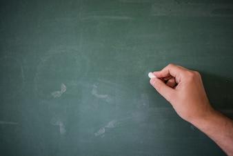 Panneau / tableau noir blanc, écriture à la main sur une planche de craie verte tenant de la craie, une grande texture pour le texte. Main d'enseignant tenant la craie devant un tableau vierge. Écriture manuelle avec copyspace pour le texte. Belle texture.