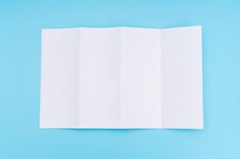 Papier carré blanc quadruple sur fond bleu.