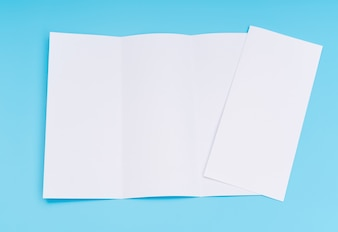 Papier de modèle blanc à trois faces sur fond bleu.