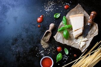 Parmesan recette de pâtes avec un morceau de fromage et de pâtes crues et d'autres ingrédients