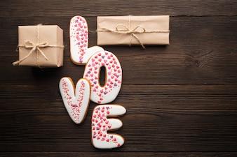 """Parole """"amour"""" avec des cadeaux brunes sur une table en bois"""