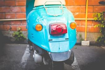 Partie arrière d'un scooter bleu, d'un ton vintage et d'un style rétro