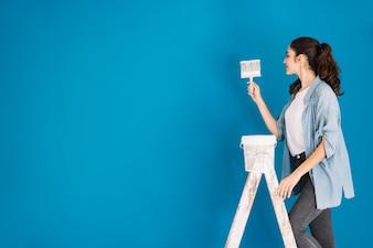 Peindre le concept avec une femme sur une échelle