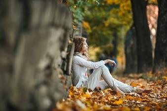 Pensive jeune femme assise sur les feuilles sèches