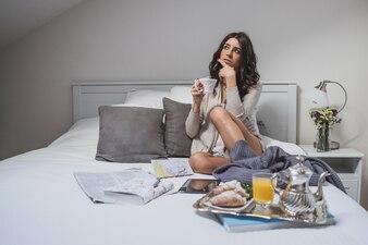 Pensive jeune femme avec tasse de café à la main