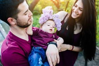 Père tenant un bébé tandis que sa mère met une couronne