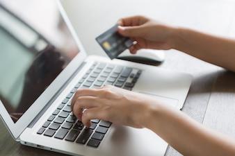 Personne à écrire sur un ordinateur portable avec une carte de crédit