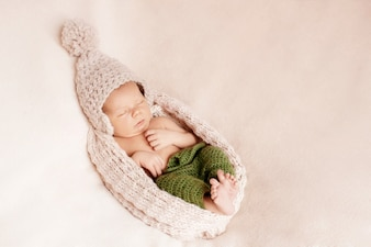 Petit bébé caché dans un bonnet de laine