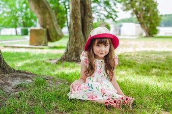 Petite fille assise sur le sol avec un chapeau