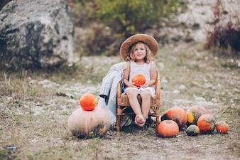Petite fille charmante dans un chapeau de paille, chaise en osier, citrouilles, automne