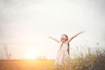 Petite fille mignonne asiatique debout au milieu du champ de fleur pourpre su