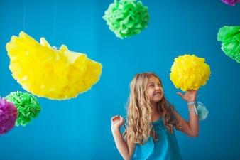 Petite fille mignonne jouant avec des fleurs colorées à l'intérieur