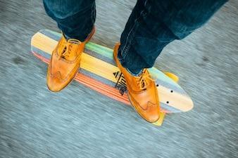 Planche à roulettes avec des chaussures en cuir