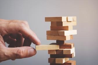 Planification, risque et stratégie dans les affaires, les hommes d'affaires et les jeux d'ingénieurs mettant un bloc en bois sur une tour.