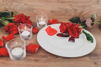 Plate avec des couverts et des roses et des bougies allumées en arrière-plan