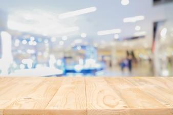 Plate-forme d'espace vide en bois vide avec un centre commercial flou ou un fond de centre commercial pour le montage de l'affichage du produit. Bureau en bois avec copie.