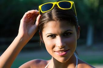 Portrait d'une jeune femme belle dans un parc avec des lunettes de soleil jaunes