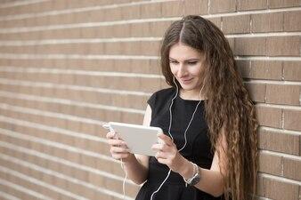 Portrait d'une jeune femme heureuse écoutant de la musique sur la tablette dans la rue