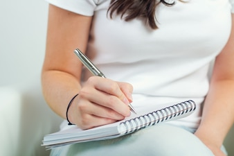 Portrait d'une jolie jeune femme prenant des notes