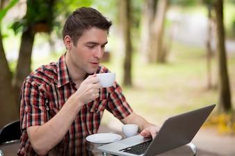 Portrait de beau jeune homme travaillant avec un ordinateur portable