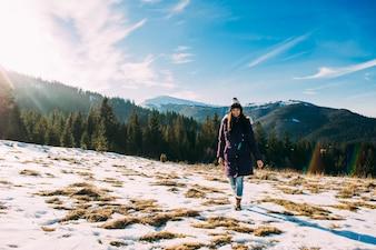 Promenade dans les montagnes, une belle fille sur fond de montagnes enneigées
