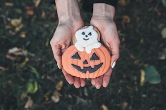 """Mains donnant un biscuit de Halloween"""