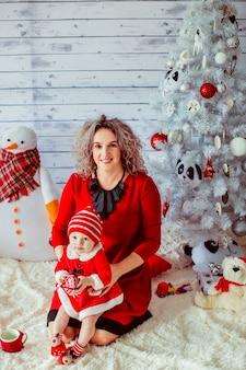 """""""Mère en robe rouge tenant une fille en bambin"""""""