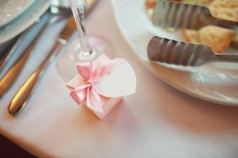 """""""Petit cadeau emballé sur table entre vaisselle"""""""