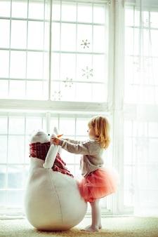 """""""Petite fille jouant avec un bonhomme de neige"""""""