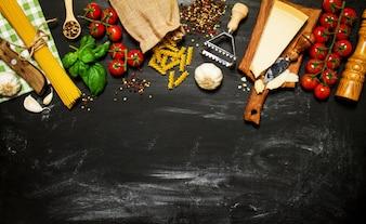 Raw pasta avec des tomates et du fromage sur une table noire
