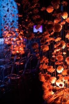 Regardez derrière les boutons de chrysanthèmes sur les fils dans des chaises en plastique