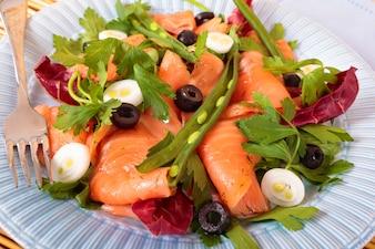 Salade de saumon fumé sur assiette bleue
